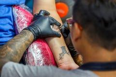 Художник татуировки конца поднимающий вверх демонстрирует процесс получать черную татуировку с краской Стоковые Фотографии RF