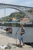 Художник улицы играя и поя перед мостом Dom Луис i стоковые фото