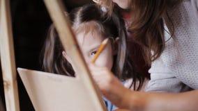 Художник учит, что маленькая девочка красит на холсте Студия чертежа акции видеоматериалы