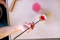 Художник человека смешивает цвета перед картиной на студии краски искусства Художник в его paintbrush удерживания руки смешал кра стоковое фото rf