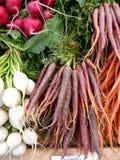 хуторянин морковей выходят пурпуровые овощи вышед на рынок на рынок Стоковая Фотография RF