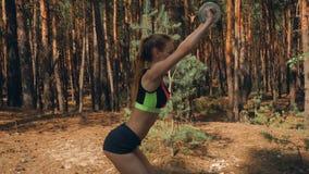 Худенькая девушка спорта в красочных коротких встряхиваниях верхней части и шортов подпирает сток-видео