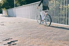 Худенькая женщина ехать велосипед города на солнечном утре стоковое фото