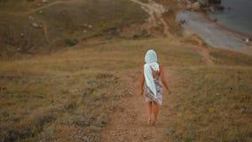 Худенькая молодая дама в головном платке и платье идет вниз в горы к морю акции видеоматериалы