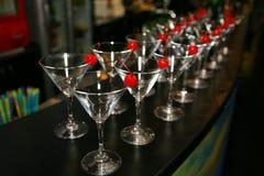 Худенькие строки пустых стекел коктеиля на баре Декоративная красная вишня Стоковая Фотография