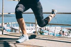 Худенький делать девушки спорт сидеть-поднимает на пляже Стоковое Фото