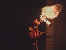 Художник выставки огня дышает огнем в темноте стоковое фото rf