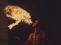 Художник выставки огня дышает огнем в темноте стоковое изображение rf