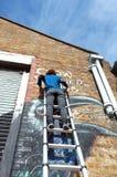 Художник граффити красит стену здания Стоковые Изображения