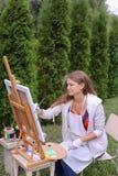 Художник девушки красит изображение и сидит на стуле на сторонах мольберта t Стоковое фото RF
