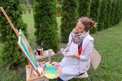 Художник девушки красит изображение и сидит на стуле на сторонах мольберта t Стоковое Изображение