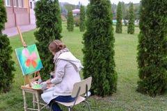 Художник девушки красит изображение и сидит на стуле на сторонах мольберта t Стоковые Изображения RF