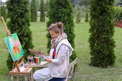 Художник девушки красит изображение и сидит на стуле на сторонах мольберта t Стоковая Фотография RF