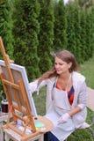 Художник девушки красит изображение и сидит на стуле на сторонах мольберта t Стоковое Фото