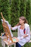Художник девушки красит изображение и сидит на стуле на сторонах мольберта t Стоковая Фотография