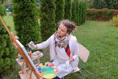 Художник девушки красит изображение и сидит на стуле на сторонах мольберта t Стоковое Изображение RF