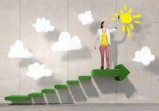 Художник девушки рисует ее положительную высоту Мультимедиа Стоковая Фотография