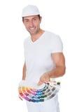 Художник держа ролик и спектр краски Стоковые Изображения