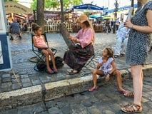 Художник женщины красит маленькую девочку на Месте du Tertre, Montmartre, Париже Стоковые Фотографии RF