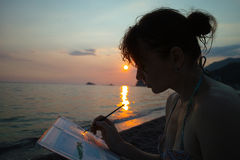 Художник женщины на заходе солнца около моря стоковые фотографии rf