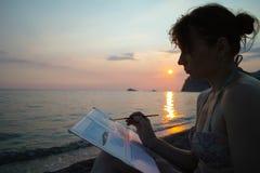 Художник женщины на заходе солнца около моря стоковое фото