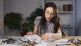 Художник женщины работает на эскизе пока сидящ в ее офисе Она носит стекла акции видеоматериалы