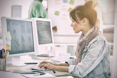 Художник используя компьютер с коллегами позади на офисе Стоковая Фотография RF