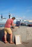 Художник красит изображение с воинским кораблем на обваловке Адмиралитейства в Санкт-Петербурге стоковые фотографии rf