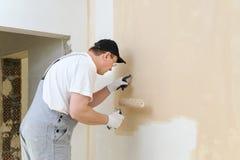 Художник красит стену в комнате Стоковая Фотография