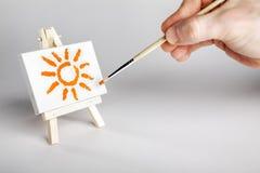 Художник крася солнце на малом массиве Стоковое Изображение RF
