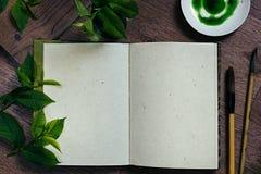 Художник рабочего места и листья зеленого цвета Представление Пустая тетрадь Тетрадь пробела времени весны Стоковое фото RF