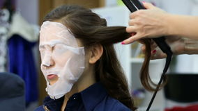 Художник стиля причёсок делает процедуру по завивая утюга волос для брюнет женщины видеоматериал