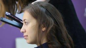 Художник стиля причёсок делает процедуру по завивая утюга волос для брюнет женщины сток-видео