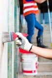 Художник с щеткой и краска на строительной площадке Стоковое Изображение
