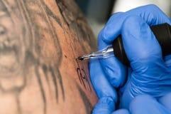 Художник татуировки делая татуировку Стоковая Фотография