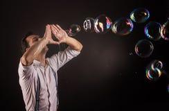 Художник дуя много пузырей мыла от его рук Стоковое Изображение RF