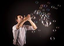 Художник дуя много пузырей мыла от его рук Стоковое фото RF