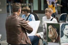 Художник улицы красит портрет мальчика на квадрате Лестера Стоковое фото RF