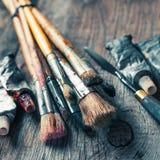 Художнические paintbrushes, трубки краски масла, ножа палитры на старой стоковые фотографии rf