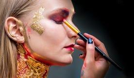 Художнический профессионал составляет прикладывает тень глаза красивейшее woma стоковая фотография rf