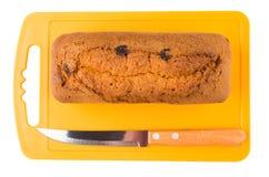 Хлебец булочки с изюминкой и ножом на оранжевой разделочной доске Стоковые Изображения RF
