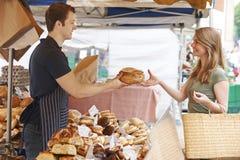 Хлебец клиента покупая от стойла хлеба рынка Стоковое Изображение RF