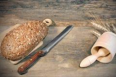 Хлебец хлеба хлопьев с зернами и нож slicer в деревенском still-l стоковая фотография