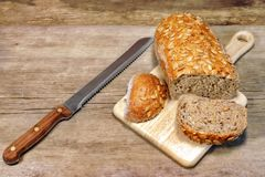 Хлебец хлеба хлопьев с зернами и нож slicer в деревенском still-l стоковое изображение rf