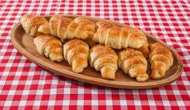 Хлебопекарня круассана на таблице teakwood на красном и белом backgr волокна Стоковая Фотография