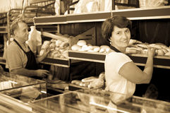 Хлебопеки позитва зрелые с свежим хлебом в хлебопекарне Стоковое Изображение RF