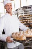 Хлебопек держа поднос хлеба Стоковая Фотография