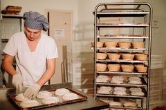 Хлебопек делает ручные взрезы на тесте для хлеба Изготовление хлеба bakersfield стоковое фото