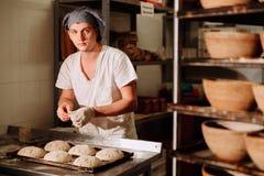 Хлебопек делает ручные взрезы на тесте для хлеба Изготовление хлеба bakersfield стоковая фотография