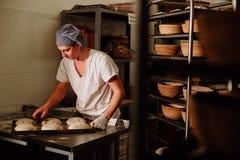 Хлебопек делает ручные взрезы на тесте для хлеба Изготовление хлеба bakersfield стоковые фотографии rf